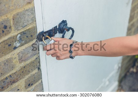 A female hand is touching a padlock on a shed outside in a garden