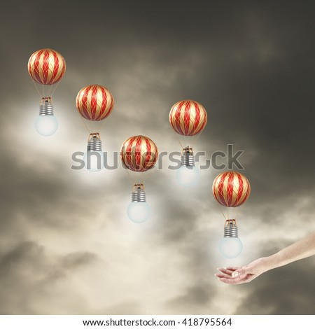 A female hand releasing hot air balloons with light bulb into a dramatic surreal sky for the concept of lighting up the future. - stock photo