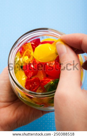 a female hand taking a candy from a jar filled with candies - stock photo