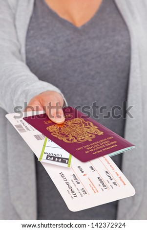 A female handing over her Passport and tickets at airport check-in. The tickets and labels are mock ups and all details are ficticious. - stock photo