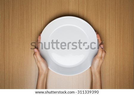 A female hands hold a empty(blank) white dish(plate) on the wood - stock photo