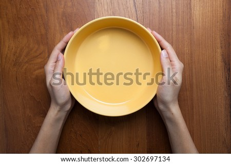 A female hands hold a empty(blank) white dish(plate) on the wood table(desk), top view at the studio. - stock photo