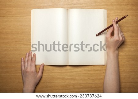 A female hands hold(grip) a vintage(old) book(note, diary) spread and hold a pencil on the wooden desk, top view at the studio. - stock photo