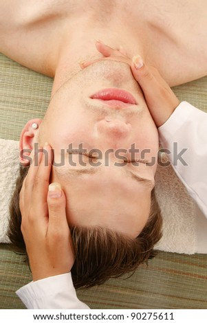 A female hands massaging man's face in a spa center