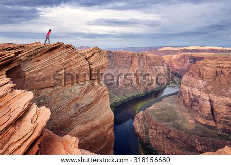 A female hiker at the edge of cliff looking down at the Colorado river. - stock photo