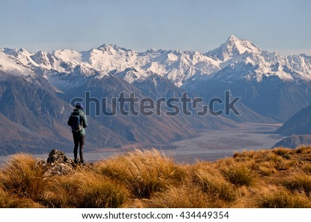 A Female Hiker Looks Towards The Southern Alps From a Mountain Top.  Mt Guy, Hakatere Conservation Park, New Zealand - stock photo