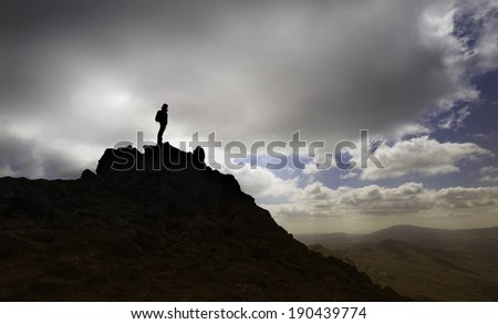 A female hiker standing on a mountain top in the Lake District, England. - stock photo