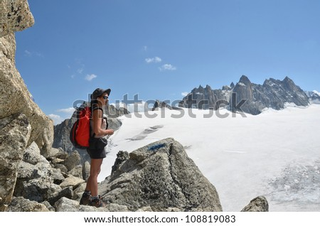 A female hiker takes in the view of high mountains and glaciers amid granite boulders on a beautiful clear day