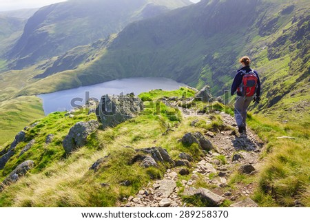 A female hiker walking down Long Stile towards Rough Crag with Blea Water in the distance in the Lake District. - stock photo