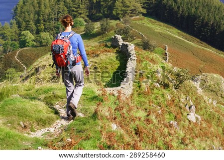A female hiker walking down towards The Rigg at Haweswater in the Lake District. - stock photo