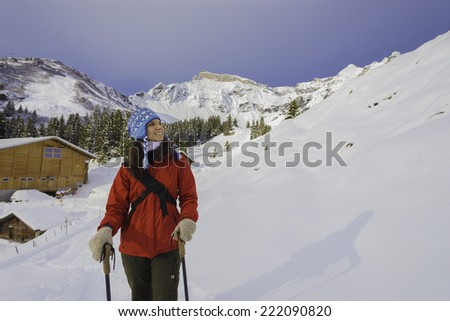 A female hiker walking through snow in the mountains - stock photo