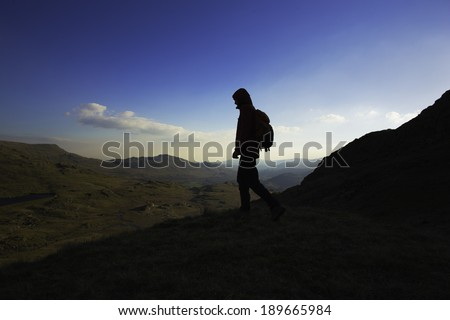 A female hiker with a backpack walking down a mountain in the Lake District, England - stock photo