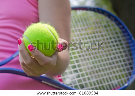 A female holding a bright yellow tennis ball - stock photo