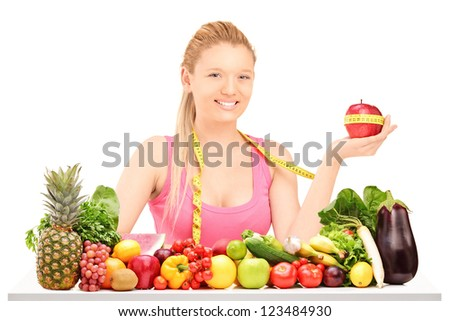 A female holding an apple wrapped with measuring tape on a table full of different fruit and vegetables isolated on white - stock photo