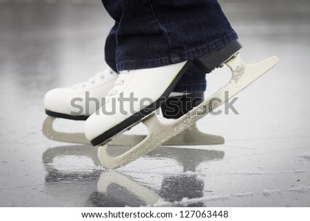 A female ice skaters skates on a frozen pond in northern Maine