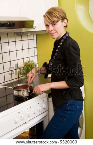 A female in the kitchen stiring a sauce over the stove.