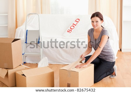 A female is preparing a cardboard box for the transport - stock photo