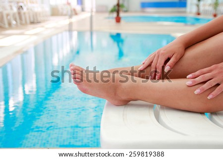 a female legs in the water pool  - stock photo