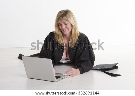 A female mature university student laying on the floor studying with a laptop