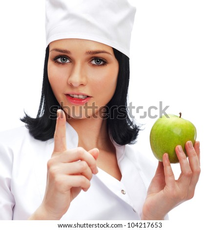 A female medical doctor holding a green apple isolated on white background
