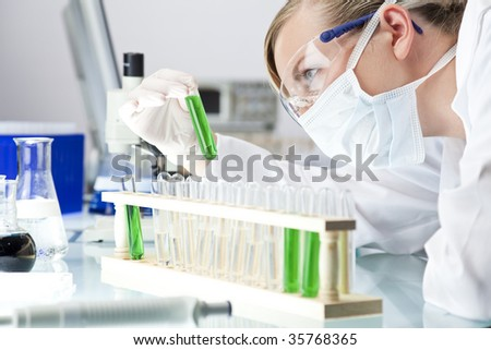 A female medical or scientific researcher or doctor looking at a test tube of green solution in a laboratory. - stock photo