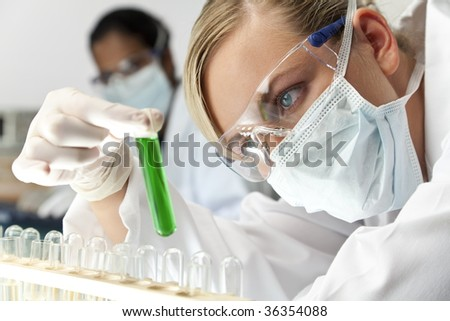 A female medical or scientific researcher or doctor using looking at a green solution in a laboratory with her Asian female colleague out of focus behind her. - stock photo