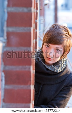 A female model looks down a sidewalk to create an interesting portrait with copyspace.