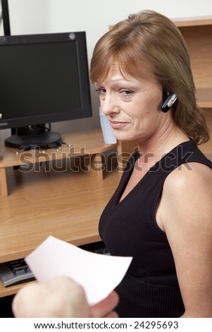 A female office worker showing fear as she receives a pink slip layoff notice - stock photo