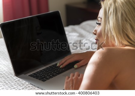 A female on a computer in a bedroom environment
