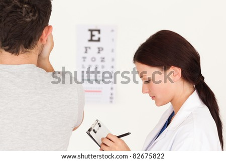 A female optician and a patient using an eye test