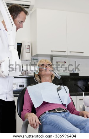 A female patient having an x-ray at the dentist - stock photo