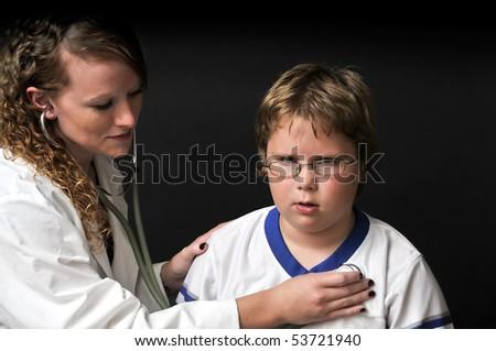 A Female Pediatrician examining a young boy - stock photo