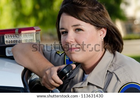 a female police officer holds the radio as she's about to talk into it. - stock photo