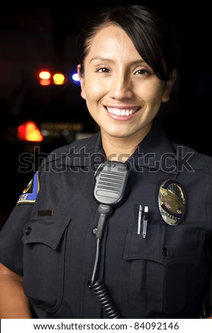 a female police officer smiling at night with her patrol car in the background. - stock photo