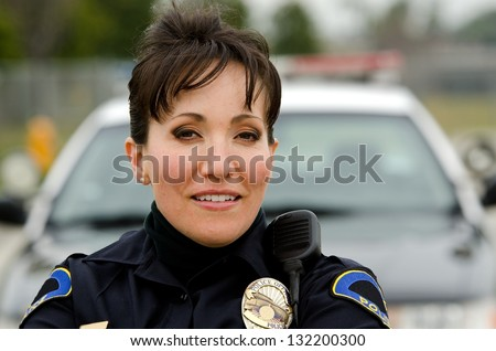 a female police officer smiling next to her police car.