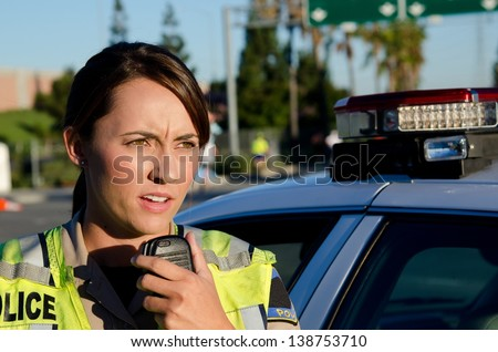 A female police officer standing next to her car about to talk on the radio. - stock photo