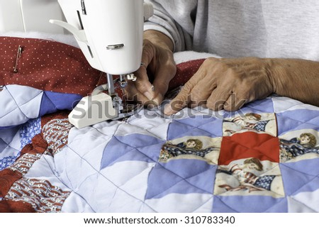 A female quilter finishes grid pattern on a patriotic quilt.
