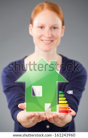 A female real estate agent offering an energy efficient green house with an A-plus energy label. - stock photo