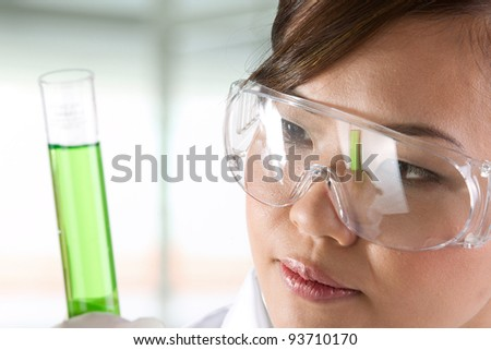 A female scientific researcher looking at a liquid solution. - stock photo