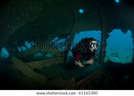 A female scuba diver exploring the inside of the SS Dunraven shipwreck. Beacon rock, Ras Mohammed national Park, Red Sea, Egypt. - stock photo