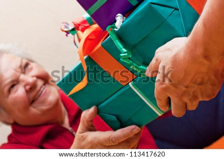 a female Senior sits and gets or give many presents closeup - stock photo