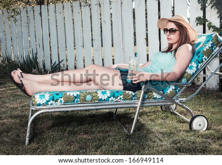 a female sitting in a chair with a glass of lemonade. - stock photo