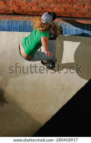 A female skateboarder performs a radical move in an empty swimming pool.