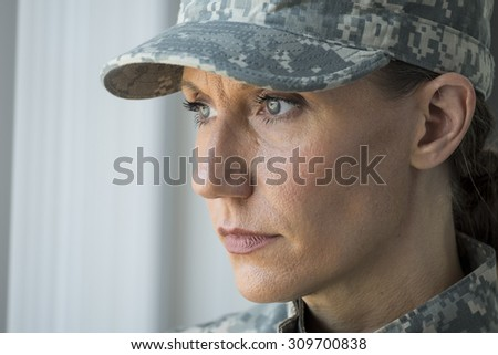 A female soldier looking out a window, blank stare - stock photo