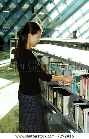 A female student checking out books at the library - stock photo