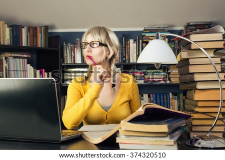 A female student sitting at the table - stock photo