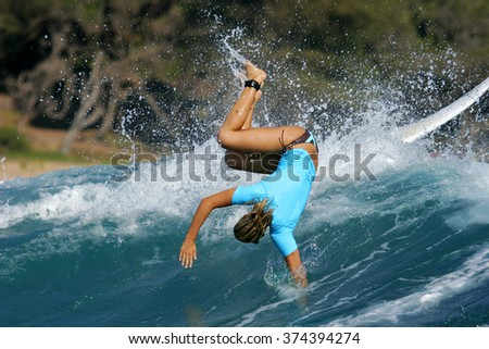 A female surfer in a blue rash vest wipes out while surfing a blue ocean wave. - stock photo