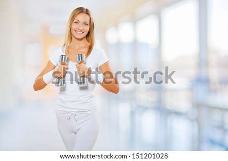 a female wearing sports clothes holding barbells - stock photo