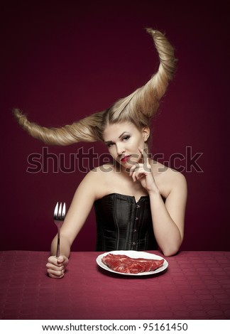 a female with a wicked demon hairstyle having a raw meat dinner