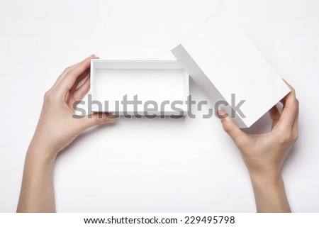 A female(woman, girl) two hands hold and open the empty(blank) white box isolated white, top view at the studio. - stock photo